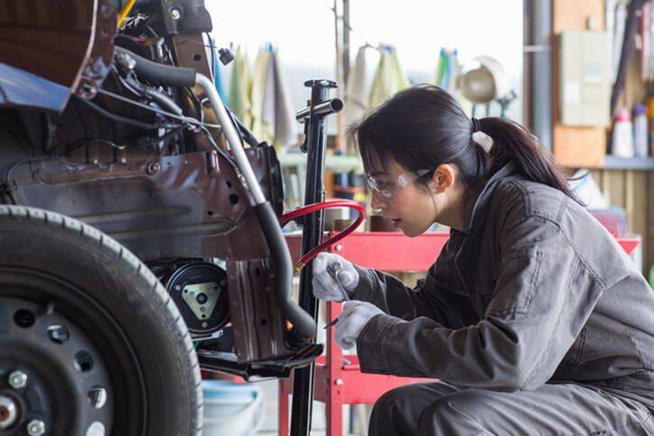 female mechanic fixing car - best auto insurance coverage mamoroneck ny